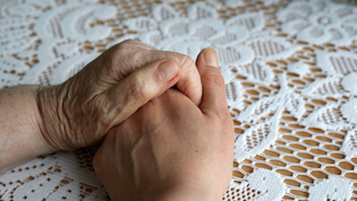 Hand holding other hand on flowery tablecloth